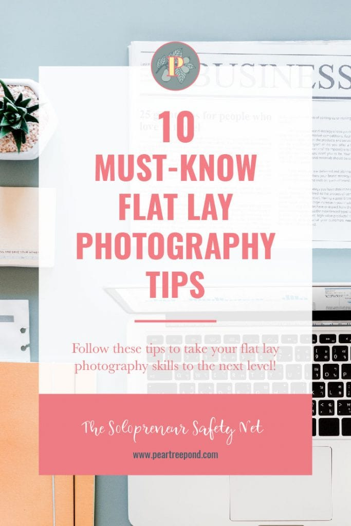 Flat lay photo of a laptop, newspaper, a potted plant and some note books on a blue desk. Text: 10 Must-Know Flat Lay Photography Tips | PearTreePond - The Solopreneur Safety Net