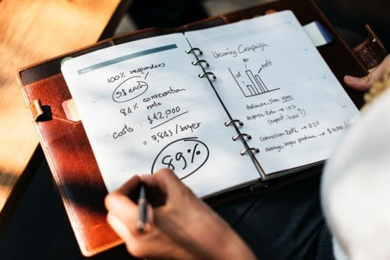 Woman with leather notebook planning a marketing campaign. | PearTreePond - The Solopreneur Safety Net