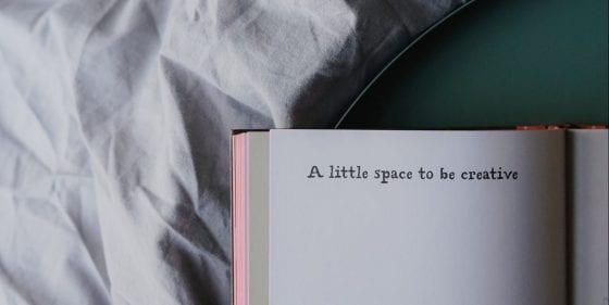Notebook lying on a bed cover; Text: A little space to be creative. | PearTreePond - The Solopreneur Safety Net