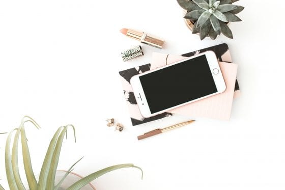 Feminine styled flat lay photo. Bird's eye view of two potted plants, an iPhone, note books, lipstick, a pen and earrings.