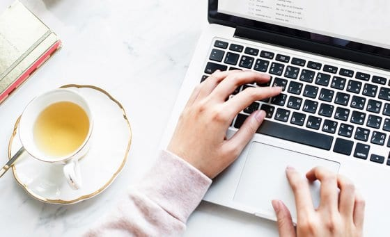 Woman working on laptop with a cup of tea next to her - The first 5 things to do your new WordPress blog | PearTreePond - The Solopreneur Safety Net