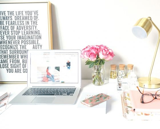 How to create a website - featured image of a laptop on a desk, surrounded by pink roses and stationary