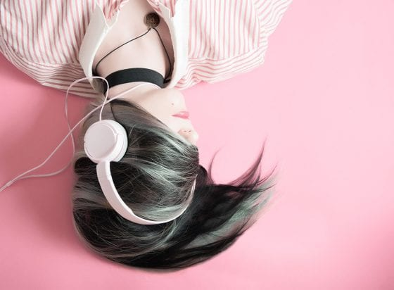 woman wearing headphones - 5 inspirational Audible audiobooks to check out now | PearTreePond - The Solopreneur Safety Net
