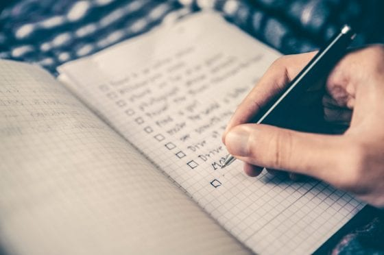 Person writing to-do list; goal setting featured image | PearTreePond - The Solopreneur Safety Net