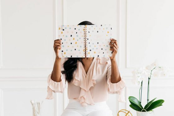 SEO fundamentals for bloggers featured image; woman looking at notebook
