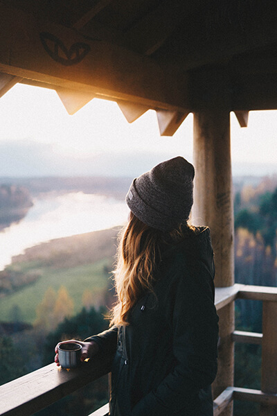 How to show up consistently, woman looking out over a forest with a cup in hand